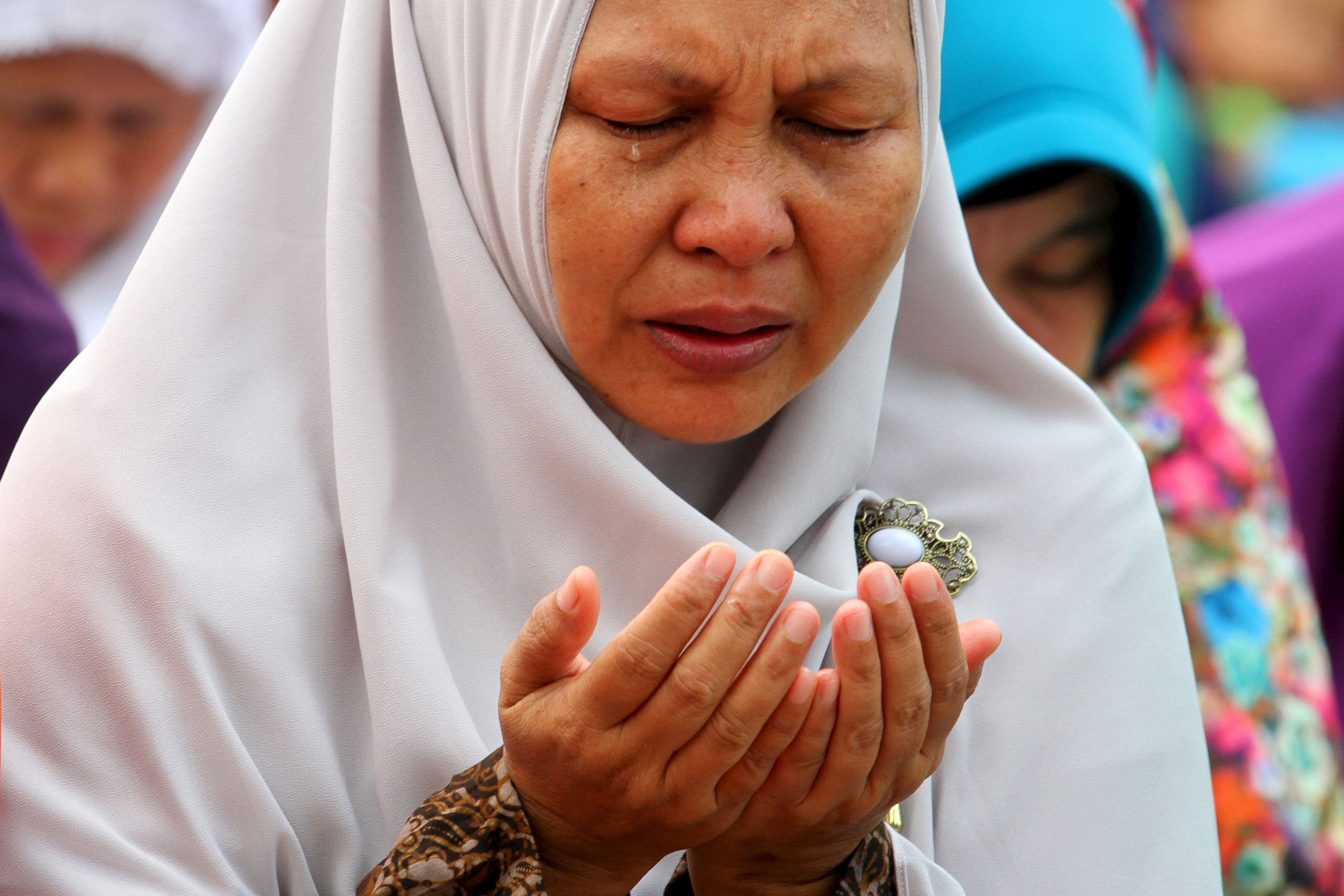 A tearful Indonesian woman in Palembang during a mass prayer for rain
