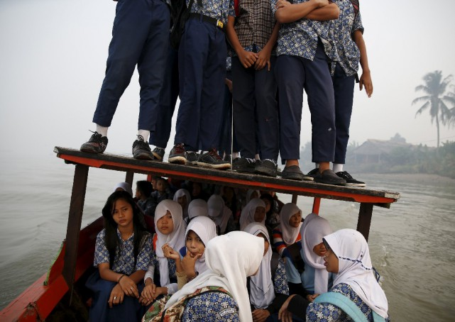 Students travelling by an open wooden boat to Palembang amidst a thick blanket of haze