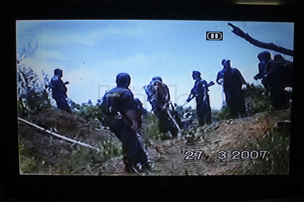 A screen shot from a video footage of police officers holding M-16 rifles while waiting for Sarawak's local council officers to destroy and seize the native's farm lands.