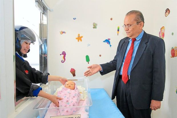 Abdul Aziz (right) and a nurse showing how a baby is placed at the baby hatch at KPJ Penang Specialist Hospital in Bukit Mertajam.