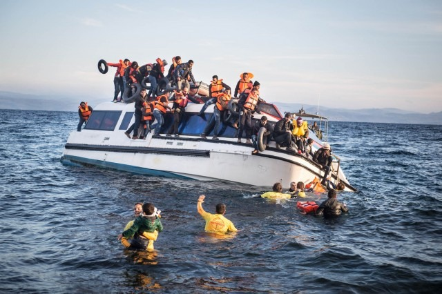 Volunteer lifeguards trying to rescue refugees on a sinking boat.