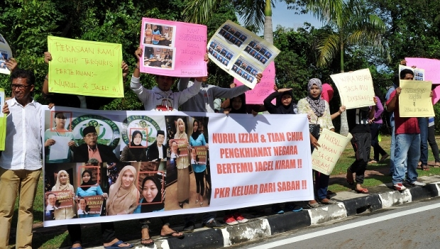Protesters hold up placards and banners to protest over the meeting between Nurul Izzah Anwar and Sulu 'princess' Jacel Kiram at the entrance of the state legislative assembly building in Kota Kinabalu, on 25 November.