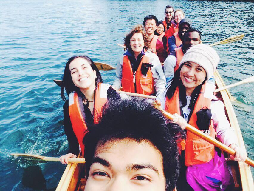 Wilderness crew taking over a Pearson-made voyager canoe over the college lake.
