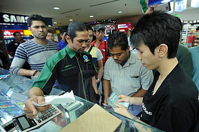 Muhammad Yusof Azmi, PPIM representative, watching on as the shop vendor returns RM5,000 back to Dipres Nasution