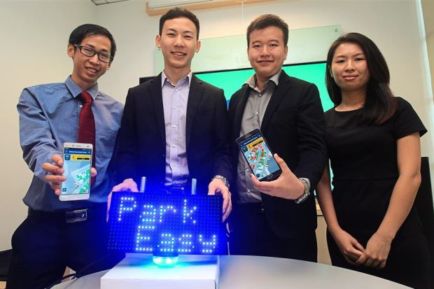 (From left) Yong, Chan, Tan and Mah showing their ParkEasy mobile app.