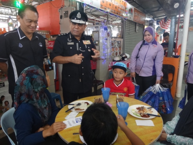 Kuching police district chief, ACP Roslan Bek Ahmad speaking to members of the public during a community policing walk around Kubah Riah, yesterday, 17 January