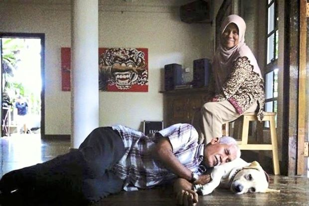Pak Mie and Mak Intan with Bobby, one of the hundreds of stray dogs they have.