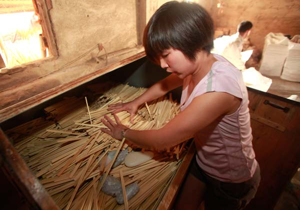 A worker at a chopstick factory showing how she polishes disposable chopsticks with chemicals.