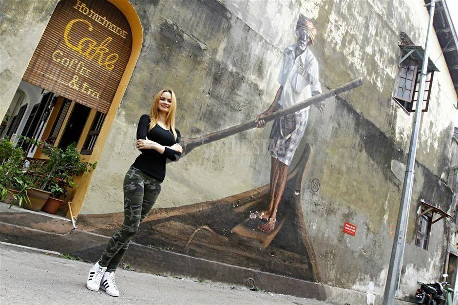 """Julia standing in front of her mural of an """"Indian Boatman"""" painted in Georgetown."""