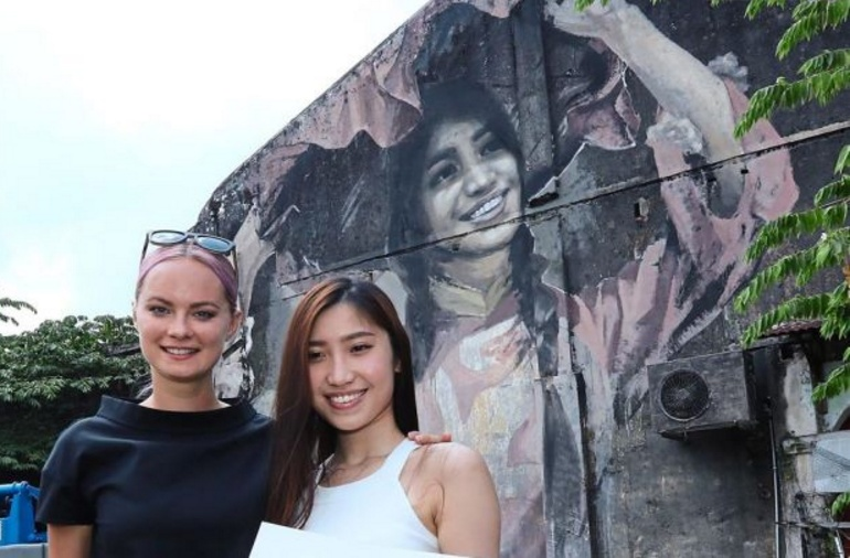 Julia with Pang (right) who was depicted in the mural in the background.