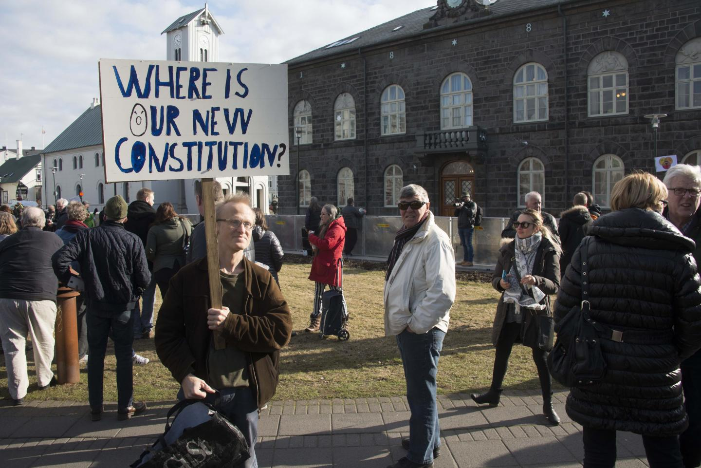 """One of the protester carrying a sign that reads, """"Where is our new constitution?"""", outside the parliament in Reykjavik, Iceland on 4 April, 2016."""
