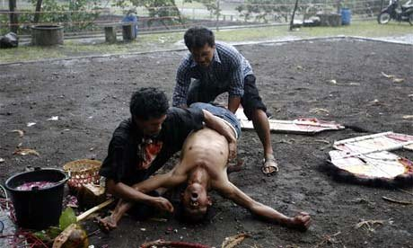 Men hold down by a spectator in a trance, Indonesia, 2008.