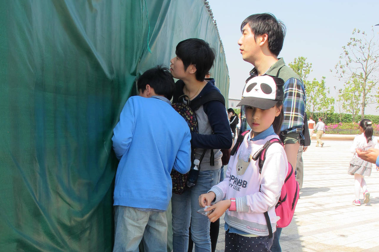 Green tarps block most views into Shanghai Disneyland, but visitors take turns peeking through gaps to glimpse the world's largest Disney Castle and a wavy structure housing a roller coaster called Tron Lightcycle Power Run.