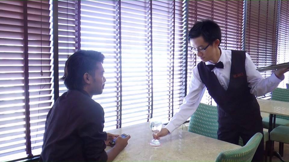 Dan Lo (right) serving a customer at Top Pot Cafe.