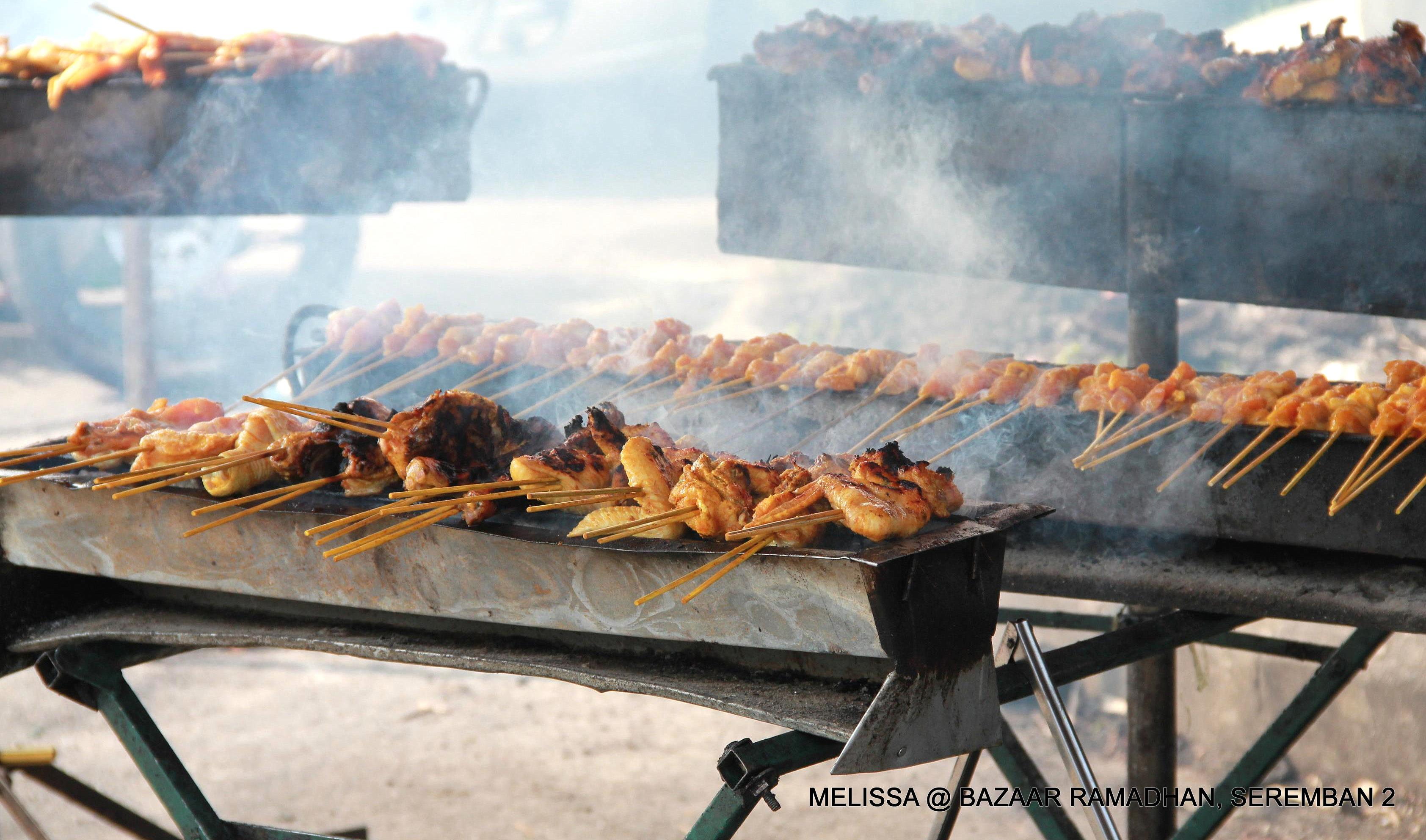 The scent of *ayam percik* and satay being grilled fill the air.