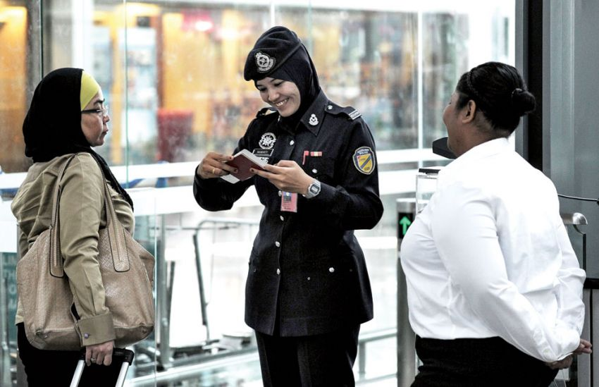 An undated file photo of a Malaysian policewoman smiling as she inspects a passenger's passport at the KLIA.