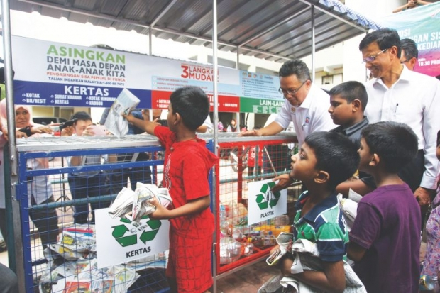 Datuk Abdul Rahman Dahlan teaching young boys how to separate their waste at the Kampung Limau PPR flats