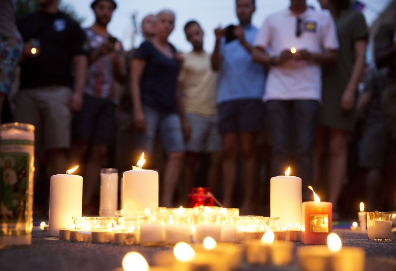 Mourners gather around candles lit during a vigil after a fatal shooting at the Pulse Orlando nightclub on Sunday.