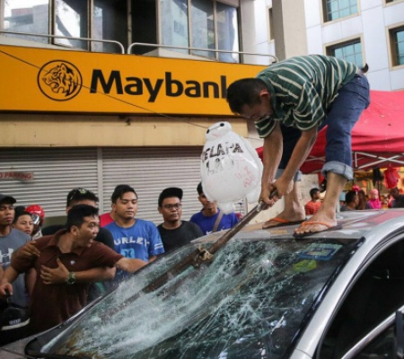 One of them is photographed smashing the windscreen of the elderly's car as the crowd gathered there watch.
