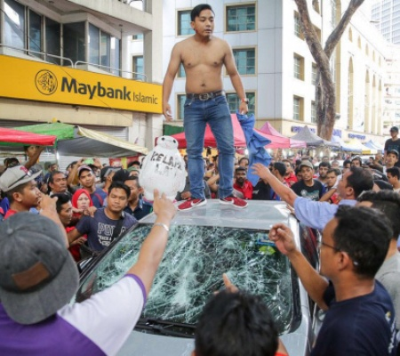 One of them was photographed standing on top of the damaged car.