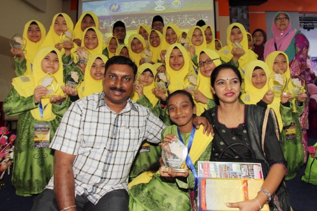 P. Thanhya Phrassanna Naidu with her parents, K. Puspiakaran and S. Parvathy photographed with her Arabic choral speaking team yesterday, 14 August