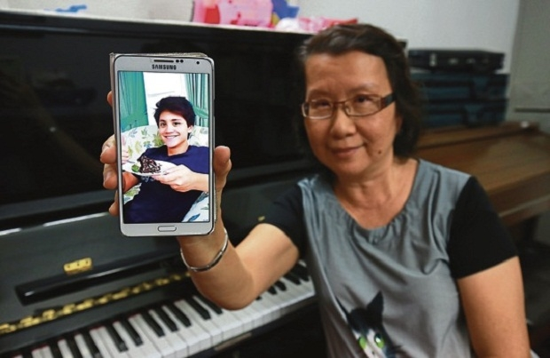 Joseph's aunt, Yim Kam Ling, showing a photograph of her nephew on her smartphone.