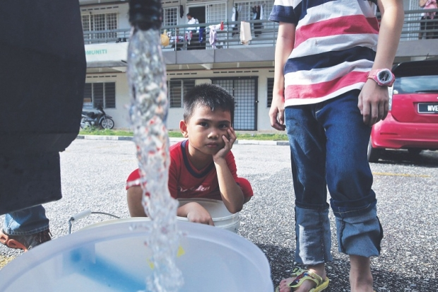 A young boy waiting for his water bucket to be filled at USJ6 on 25 September.