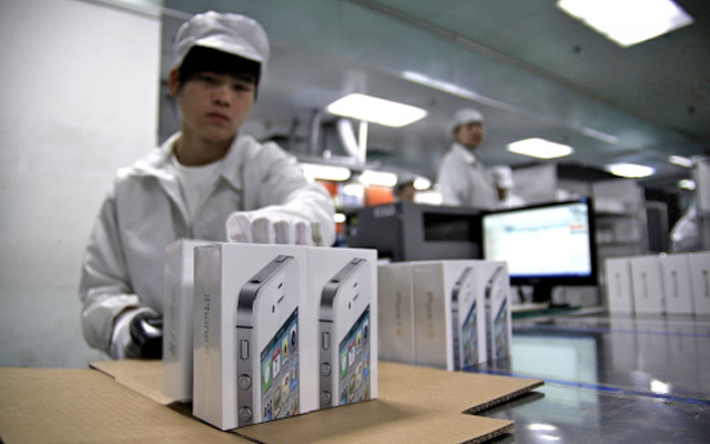 A Foxconn employee packing boxes of iPhones.