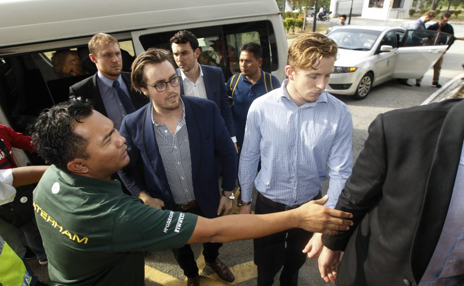 Nick Kelly, center left with glasses, and Thomas Whitworth, center right, of the nine Australian men arrested arrives at the Sepang Magistrate in Sepang.