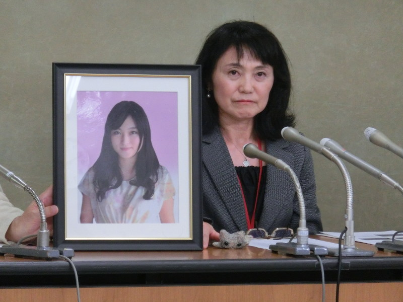 Matsuri's mother, Yukimi Takahashi, sitting next to her framed picture, at a news conference in Tokyo on 7 October 2016.
