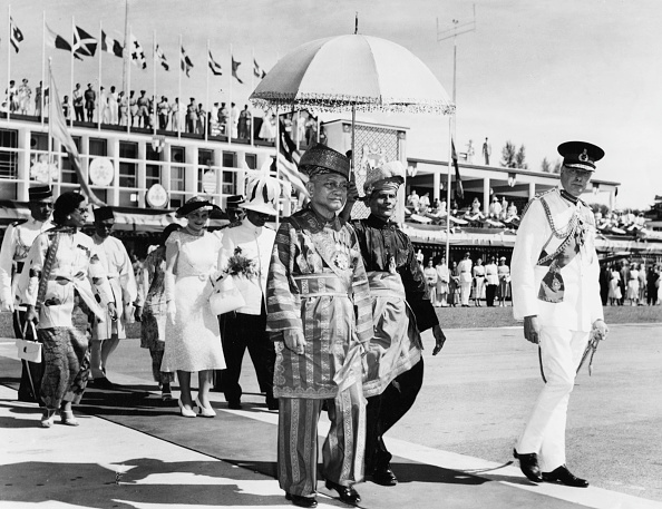 Abdul Rahman of Negeri Sembilan King of Malaysia walking to his aircraft followed by his entourage in KL, 1938.