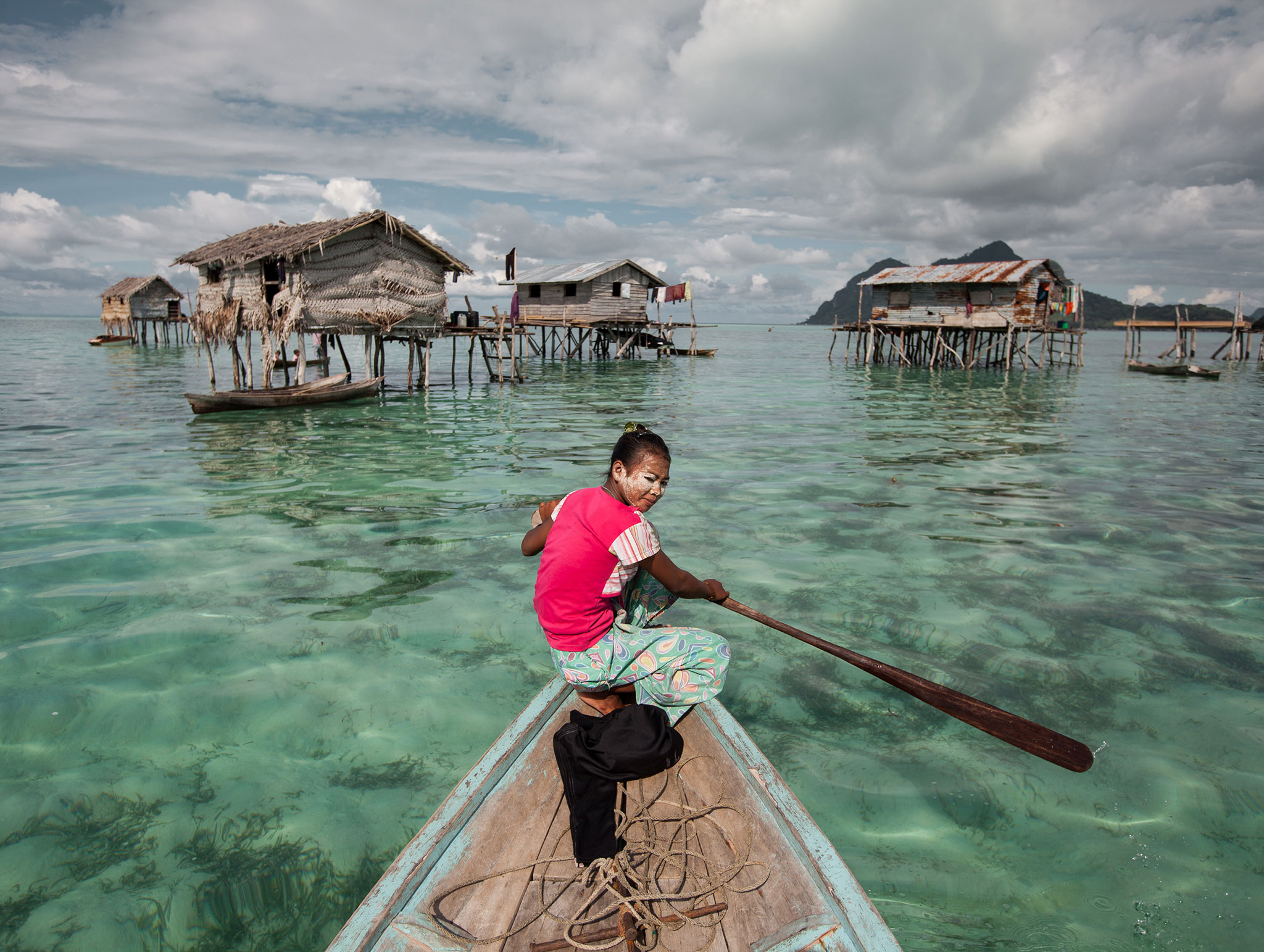 A Bajau Laut girl making her way to a friend's house.