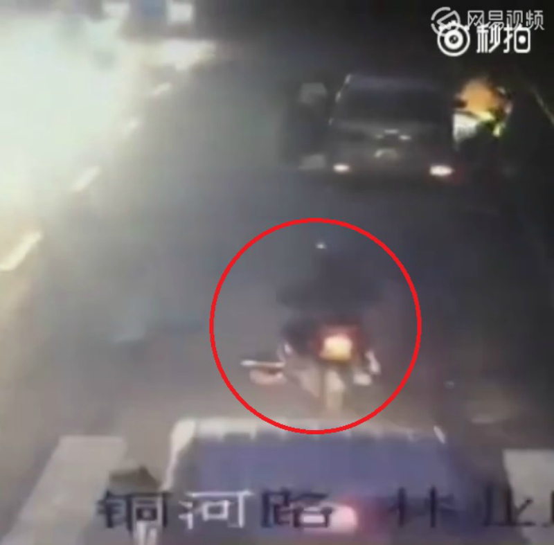 A second motorbike runs directly over Zhang's body.