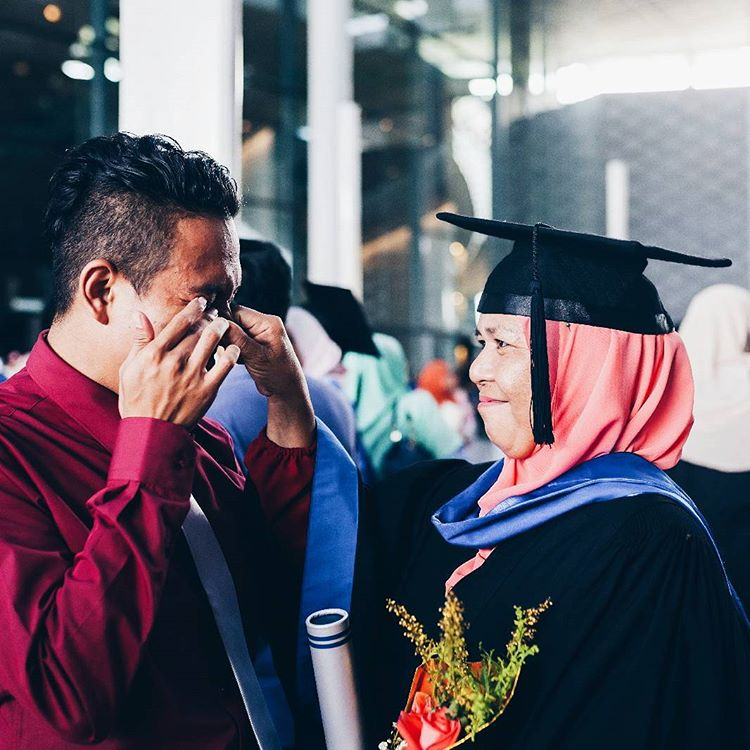 Nizam (left) in tears while his mother looks at him with pride.