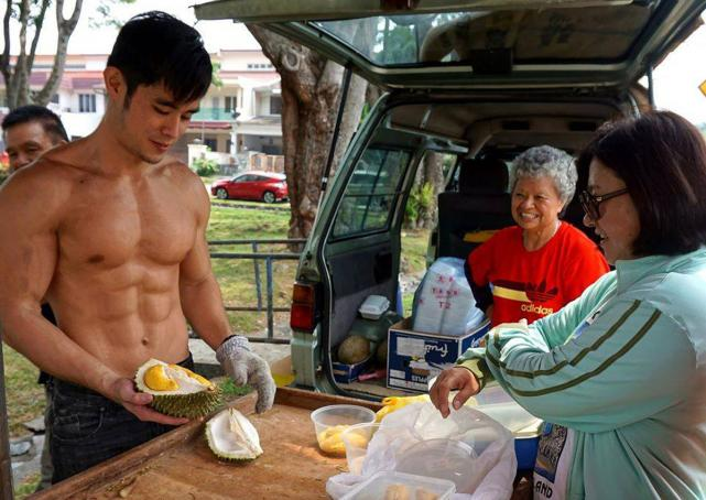 Not sure if that aunty was looking at the durians or his abs...