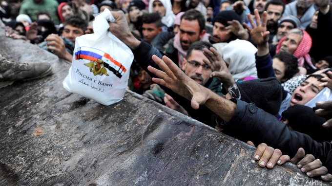 Civilians reaching out for food aid in Aleppo.