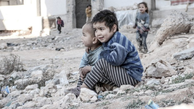 Four-year-old Esraa is sitting with her three-year-old brother Waleed on the ground, among the rocks and rubble.