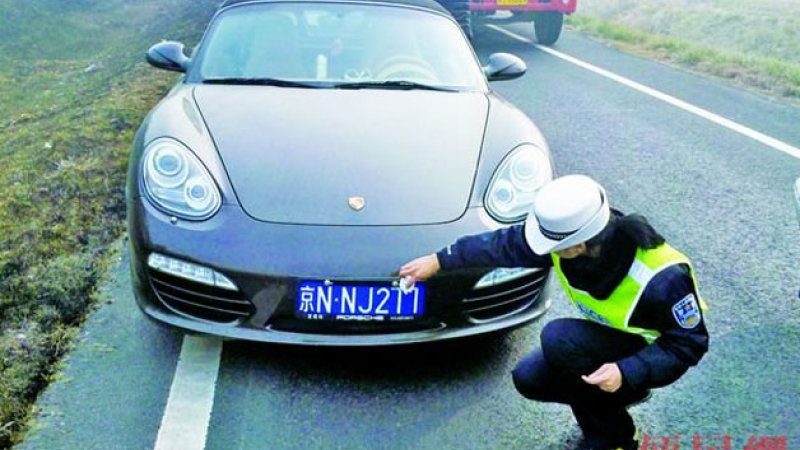 A police officer wiping off toothpaste from a Porche's license plate.