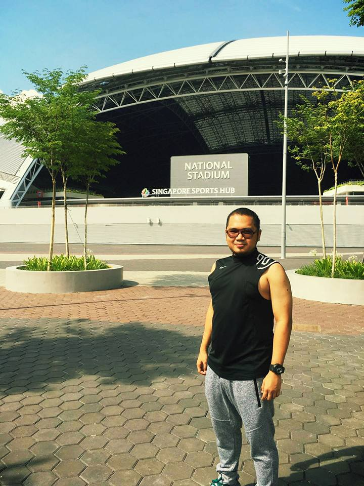 Choon Seng posing for a photo in front of Singapore Sports Hub.