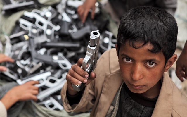 A young boy playing with a toy gun in Sana'a, Yemen.