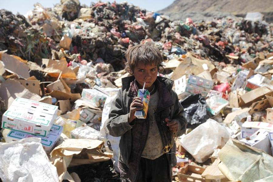 A boy photographed drinking expired juice from a pile of rubbish on the outskirts of Sana'a, Yemen, 16 November 2016