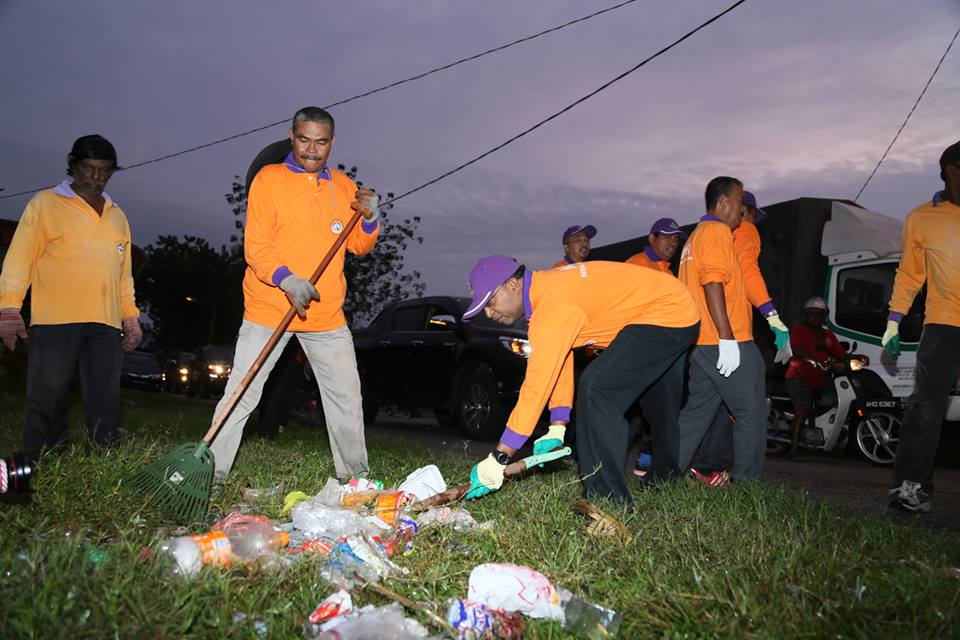 Perak Menteri Besar Zambry Kadir helping the MBI workers collect trash in Ipoh this morning.