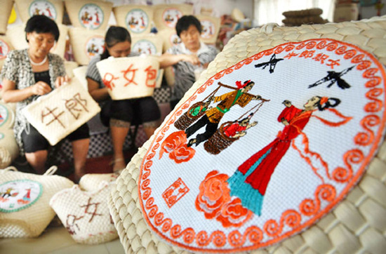 Women weave decorations onto grassmat products in preparation for Qixi Festival.