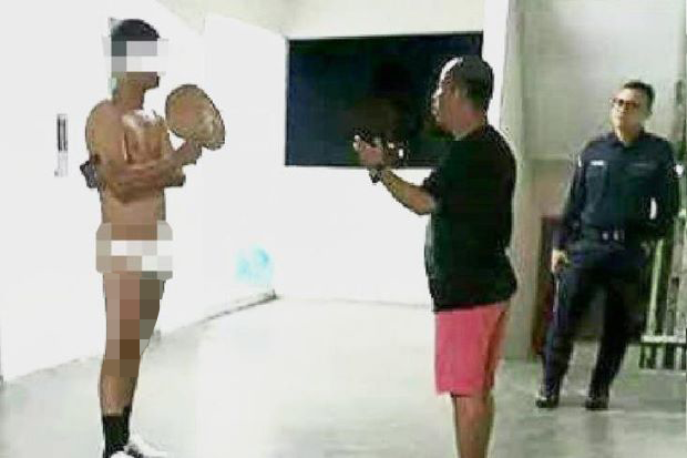 Paya Terubong JKKK member Richard Tham is seen trying to persuade the naked man to put on his clothes, while a policeman looks on.