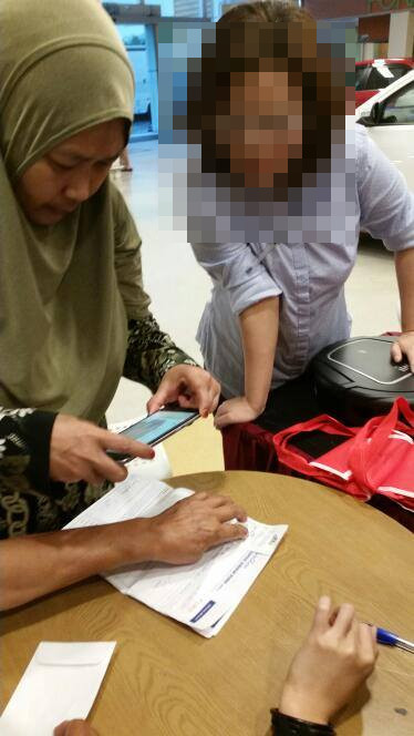 Norhaliza taking photos of the documents her dad had signed. The bespectacled lady standing beside her is the other unnamed salesperson.