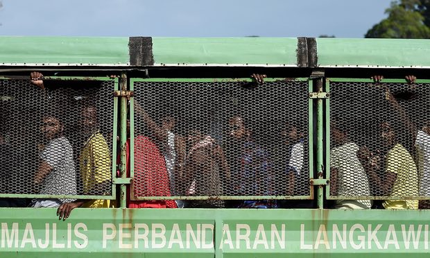 Bangladeshi and Rohingya migrants arriving at the naval base in Langkawi to be transferred to a immigration detention centre in the mainland.