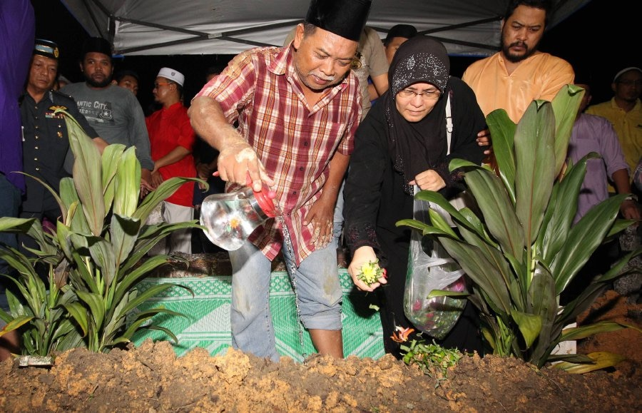 Zurfarhan's heartbroken parents performing the burial rituals on the night of the 2nd June.