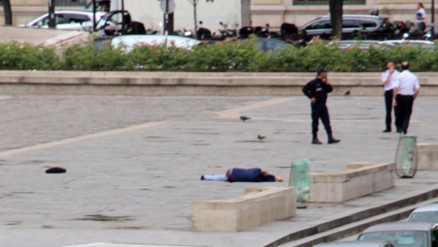 A man lies on the ground outside Notre Dame Cathedral after attacking police officers in Paris.