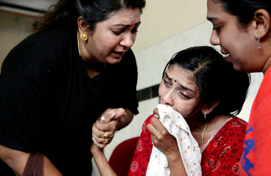 Nhaveen's mother, D. Shanti (C), is consoled by relatives at the Penang Hospital.
