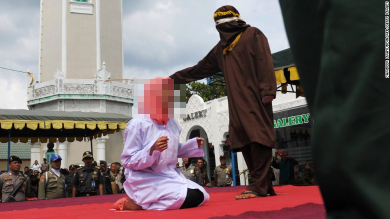 A young woman being caned in public in Banda Aceh for violating the Syariah law.